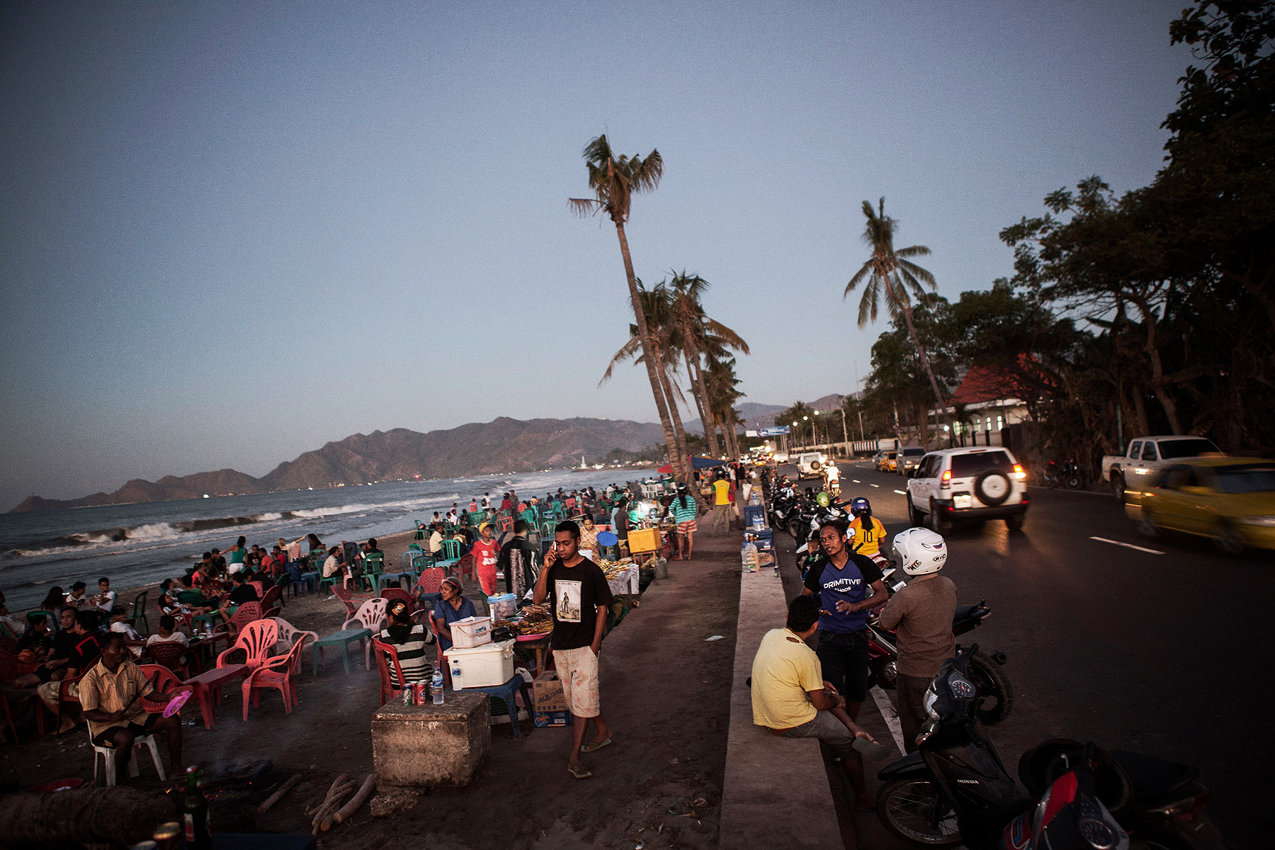 Early evening in Dili, locals gather at makeshift barbecue restaurants on the seafront.