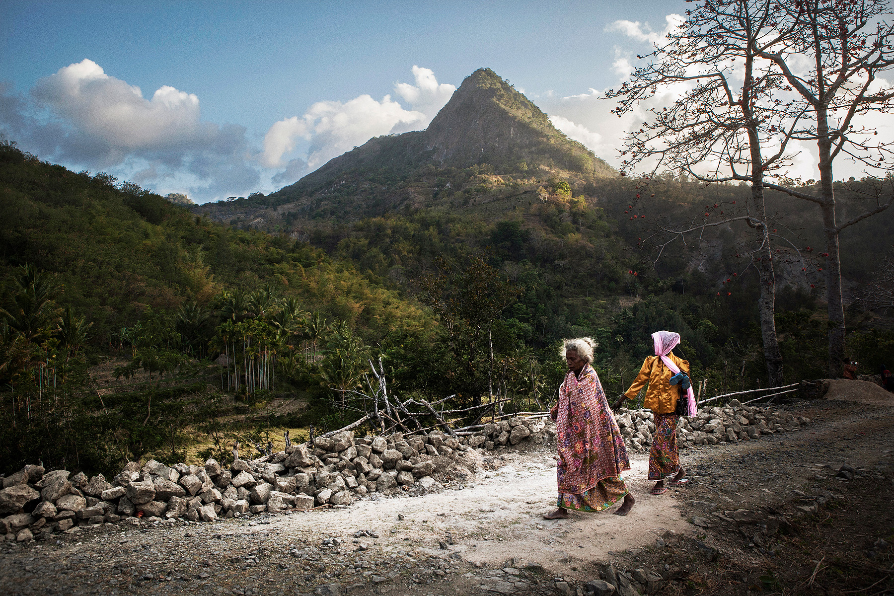 Villagers walk back to their village on a small road in Bobonaro