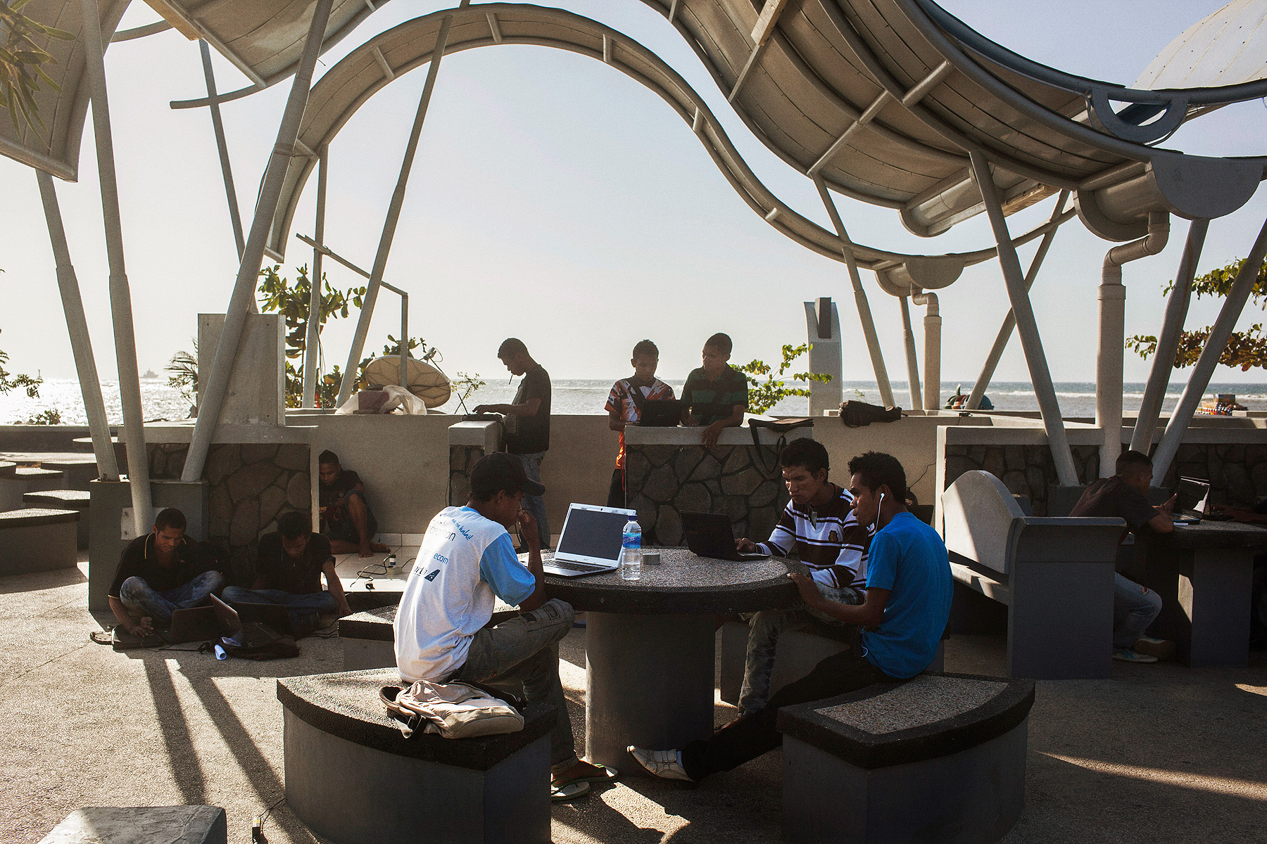 University students use their laptops at a free wifi spot on the sea front in Dili