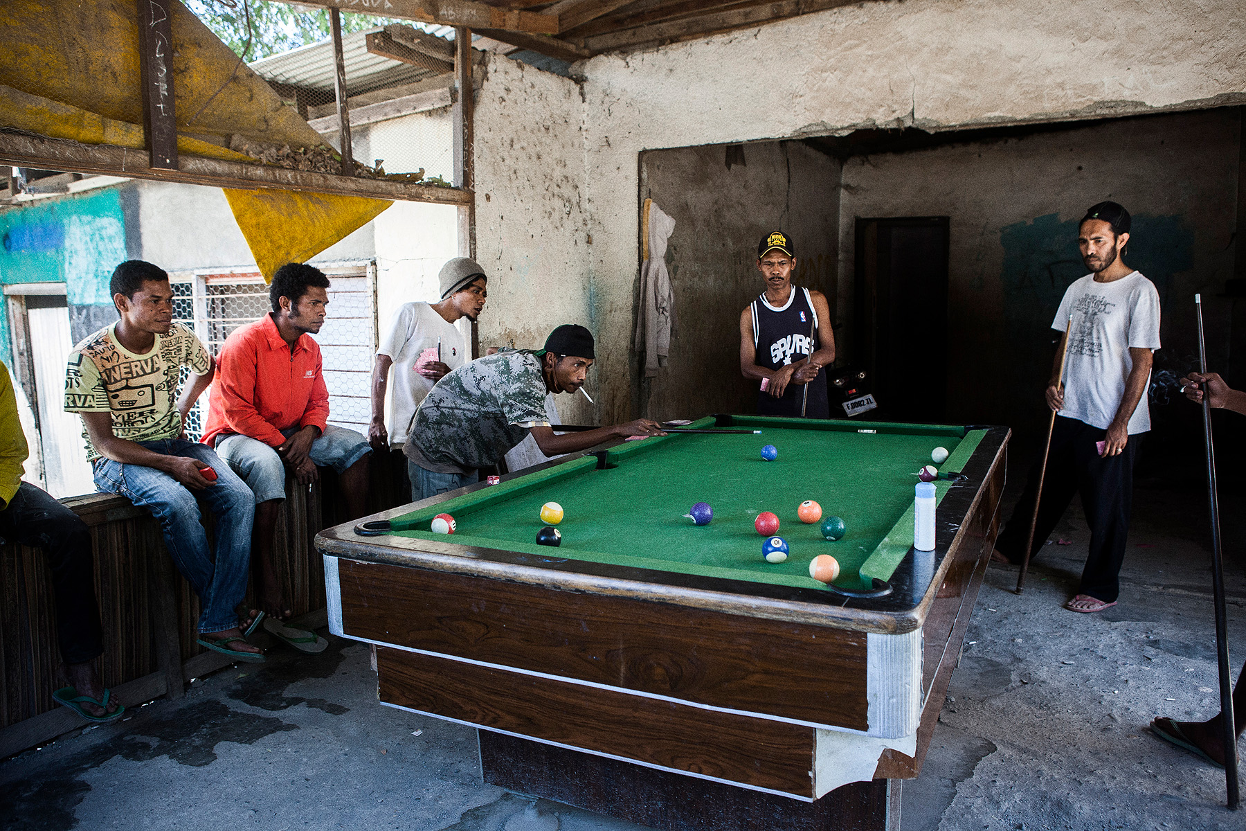 Young men play pool at on old house in Balibo