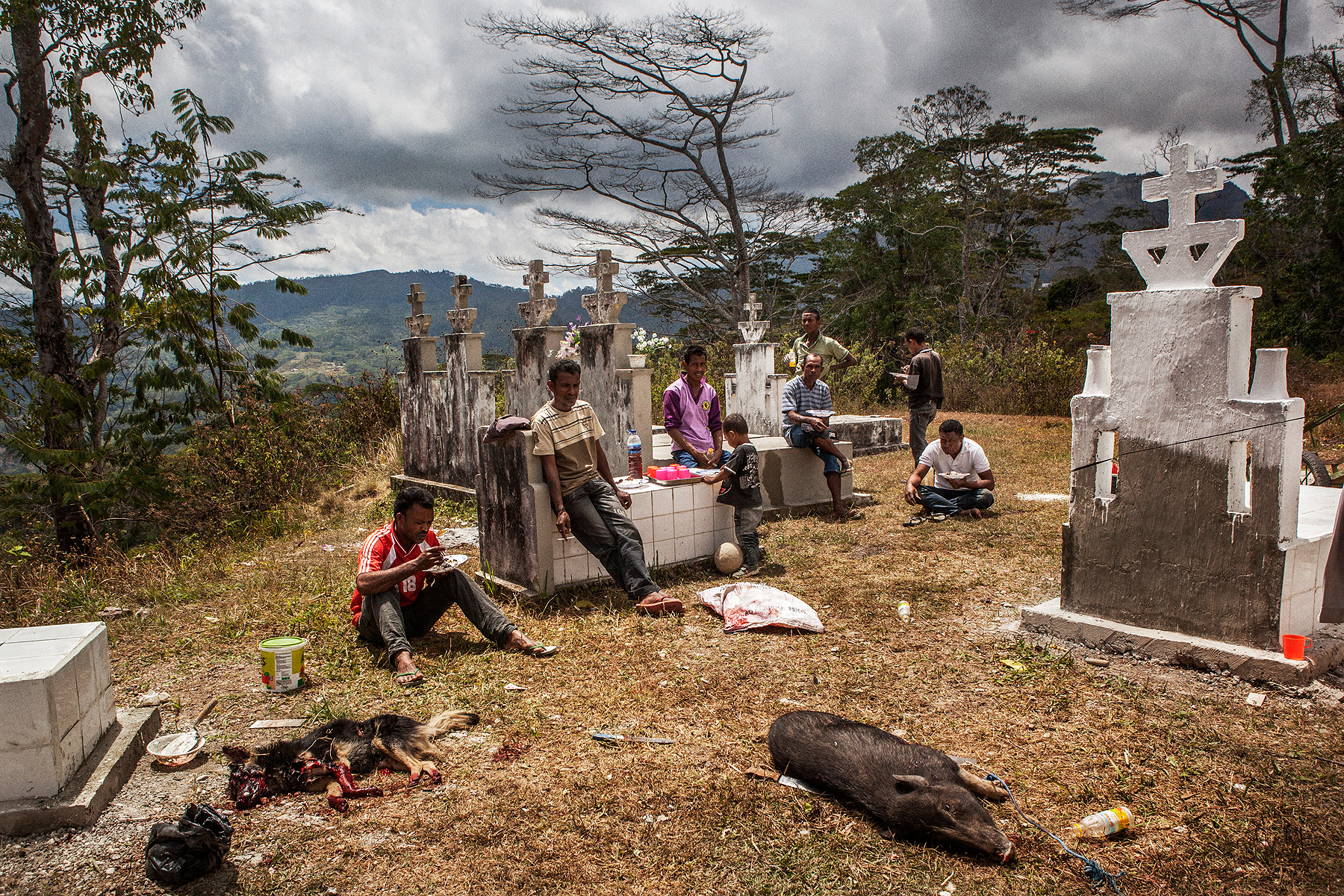 Local villagers in Atsabe wait for a ceremony to start and have their lunch after sacrificing a dog and a pig - East Timor is predominately catholic but elements of animism are incorporated into the religion