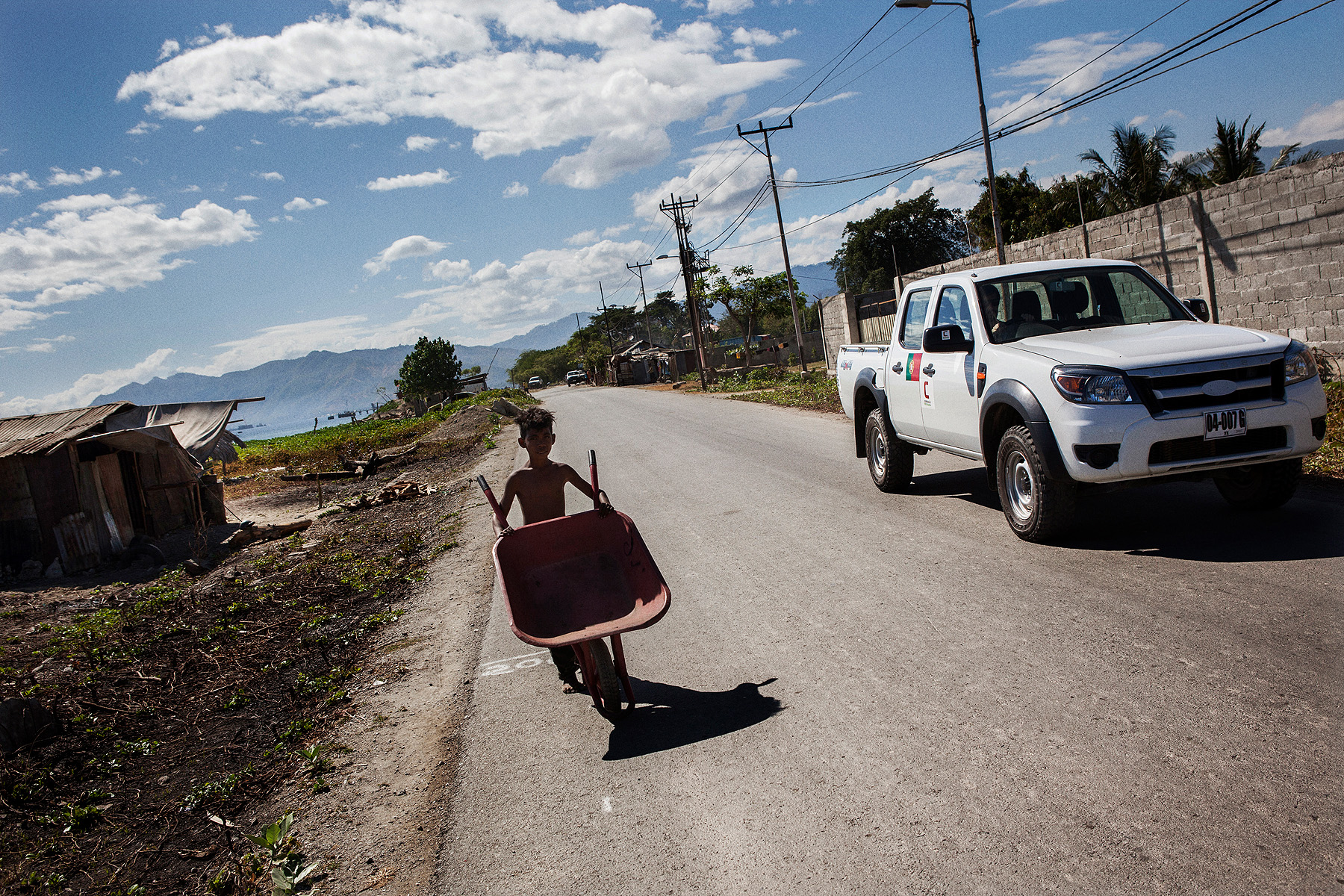 A child pushes a wheelbarrow along a Dili road on the seafront as a car from the Portuguese EU cooperation delegation goes past.